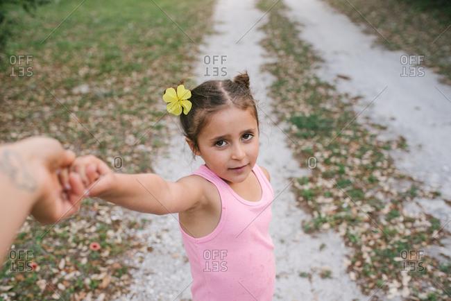 Girl with flower in her hair grasping finger of parent