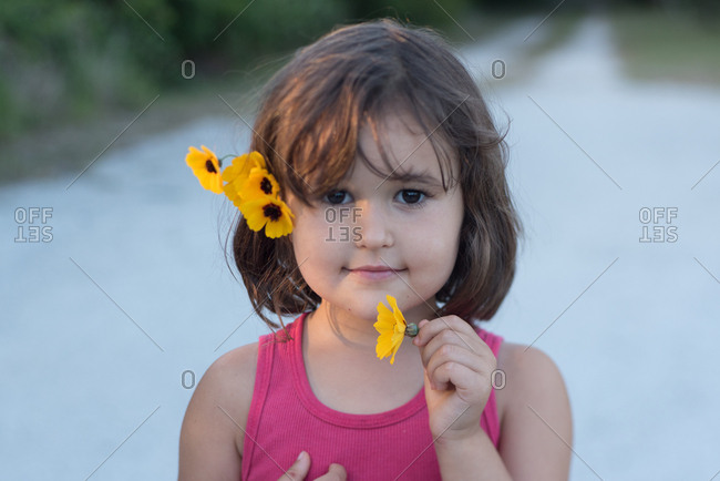 Portrait of a little girl with yellow flowers in her hair