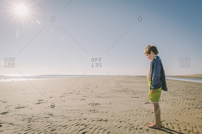 Boy standing alone on a sandy beach