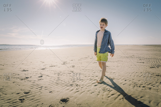 Boy walking on a sandy beach by himself