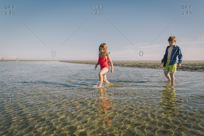 Sister and brother wading through tide on the beach