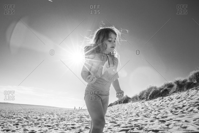 Little girl walking near sand dune