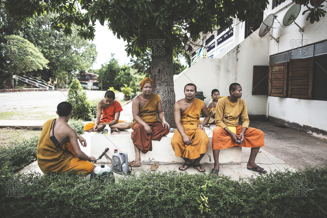 Thailand - June 19, 2015: Buddhist monks in their orange robes seen by a Buddhist temple