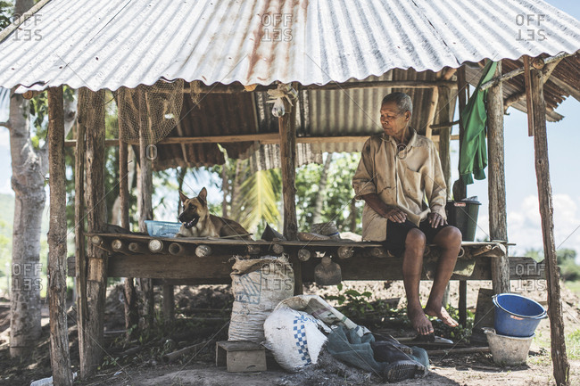Thailand - June 20, 2015: An old Thai man sitting with a dog in his shack