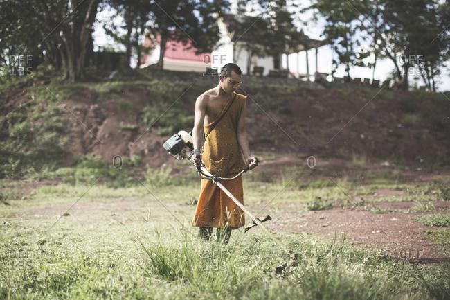 Loei Province, Thailand - June 19, 2015: A Buddhist monk cutting grass in his orange robe