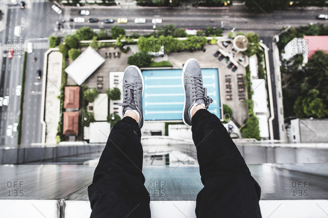 Person putting their legs out over the edge of a rooftop in Bangkok, Thailand