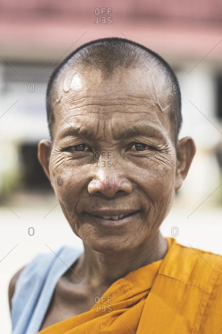 Thailand - June 19, 2015: Portrait of a smiling Buddhist monk wearing an orange robe
