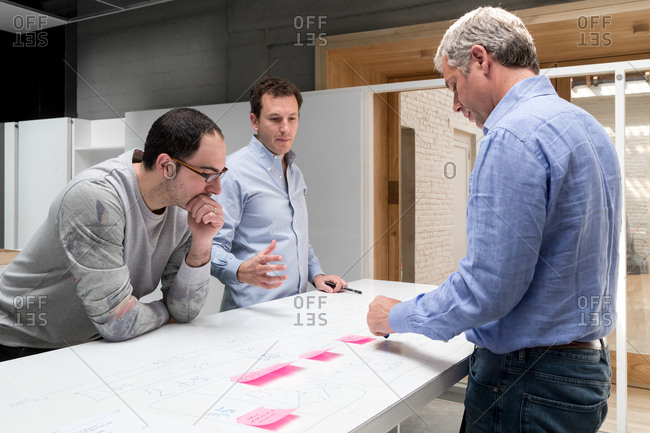 Three men discussing a plan together in an open office setting