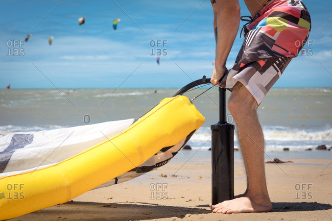 Kitesurfer on beach inflating kite