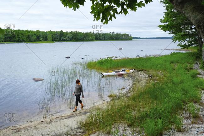 Woman walking on shoreline, Kejimkujik National Park, Nova Scotia, Canada