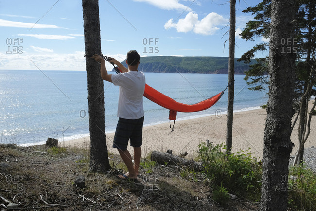 Man preparing hammock, Ingonish, Cape Breton, Nova Scotia, Canada