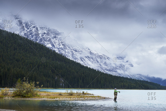 Man fly fishing in lake by snow capped mountains, Banff, Alberta, Canada