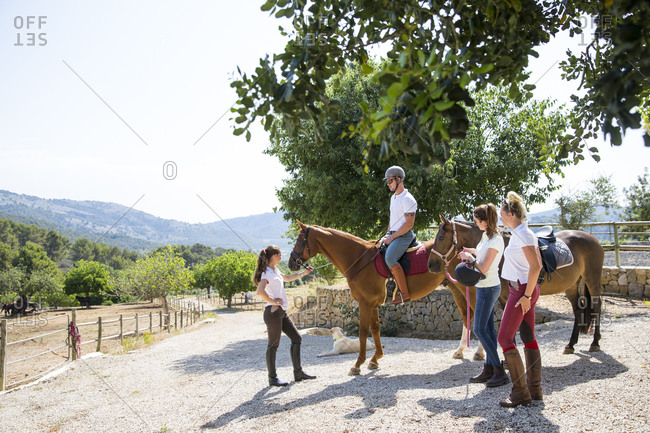 Female groom leading horse rider in paddock at rural stables