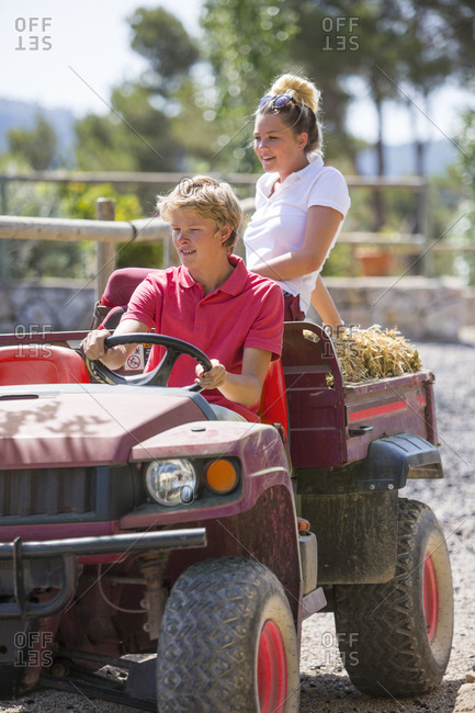 Young male and female grooms driving pick up with straw bales at rural stables
