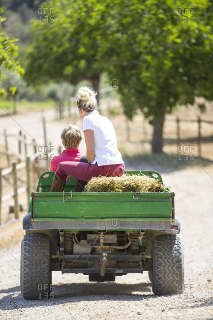 Rear view of male and female grooms driving pick up with straw bales at rural stables