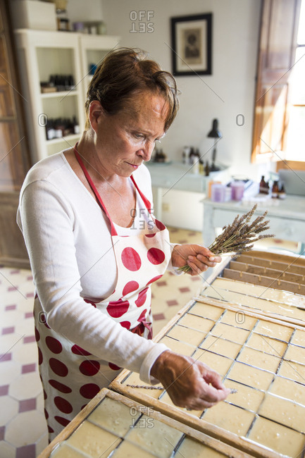 Mature woman applying dried lavender to soap bars in handmade soap workshop