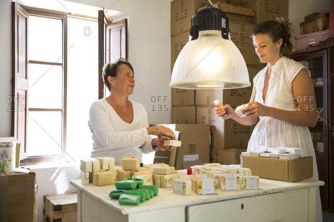 Two women packing soap products in handmade soap workshop