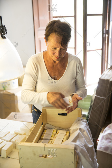 Woman packing soap bars in handmade soap workshop