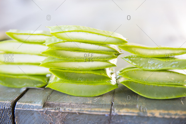 Stacked sliced aloe leaves on table in handmade soap workshop