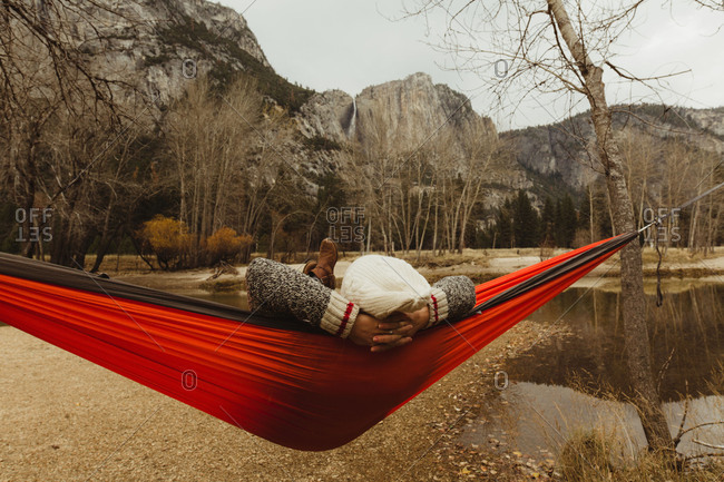 Rear view of woman reclining in red hammock looking out at landscape, Yosemite National Park, California, USA