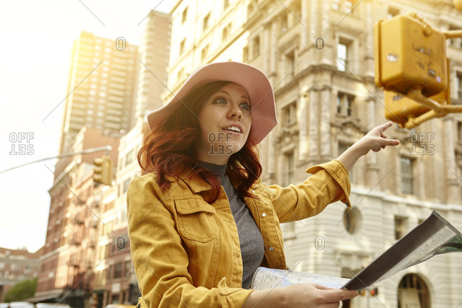 Young female tourist with long red hair hailing a cab on street, Manhattan, New York, USA