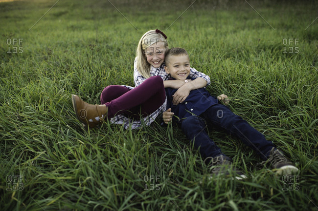 Brother and sister lying down together on grass