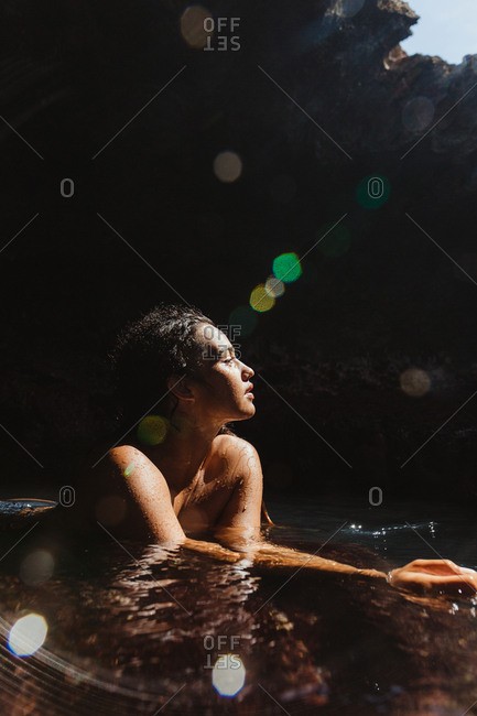Woman in water filled cave eyes closed looking away, Oahu, Hawaii, USA
