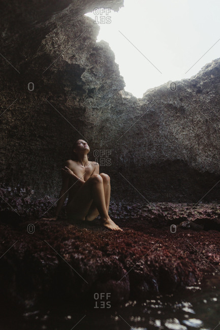 Young woman sitting on rocks, looking out of cave, Mermaid Caves, Oahu, Hawaii, USA