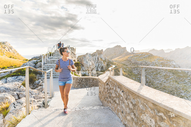 Woman on paved hilltop footpath, Mallorca, Spain