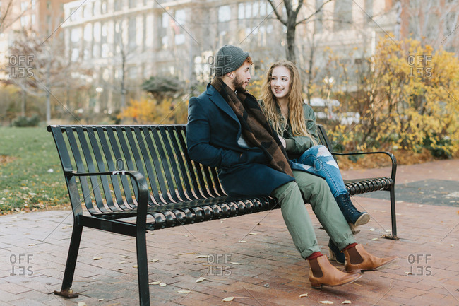 Young couple resting on park bench, Boston, Massachusetts, USA