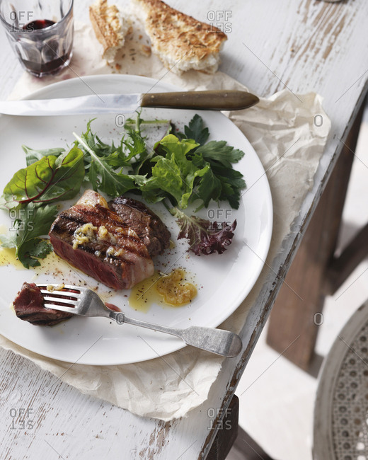 Filet mignon with garlic butter, mixed greens salad, red wine and crusty bread on plate in restaurant, close-up