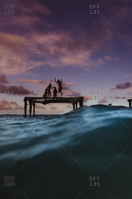 Silhouette of friends bouncing on trampoline in sea, Oahu, Hawaii, USA