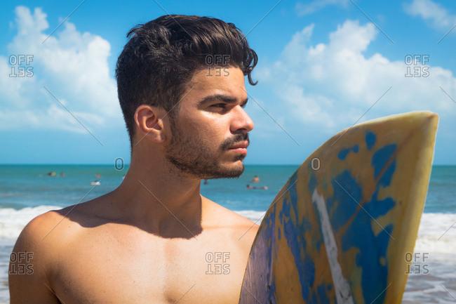 Young man on beach, holding surfboard, Fortaleza, Ceara, Brazil