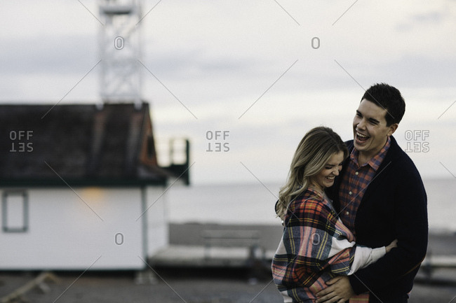 Young couple outdoors, embracing, laughing