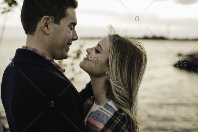 Young couple outdoors, standing face to face, smiling