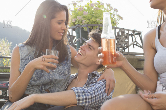 Young couple flirting at roof terrace party