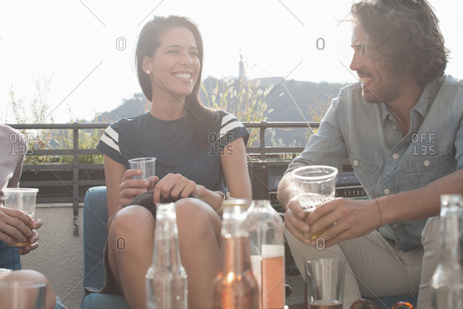Young adult friends relaxing with drinks at roof terrace party