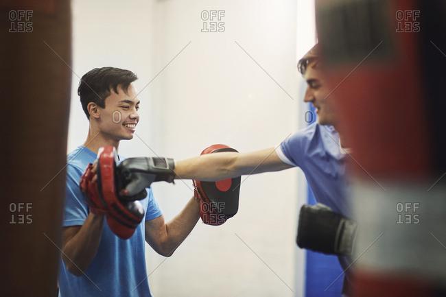 Male boxer training, punching teammate's punch mitt
