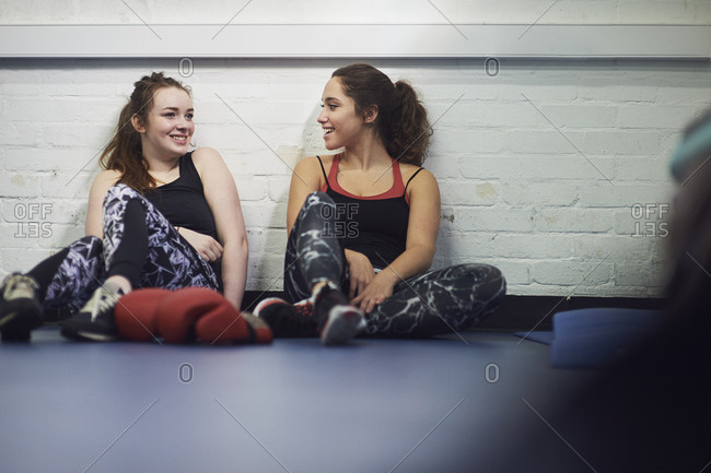 Two young female boxers sitting on gym floor chatting