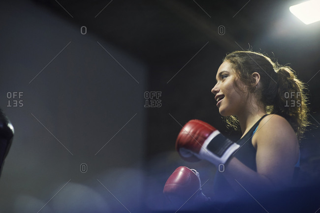 Young female boxer having boxing match in ring