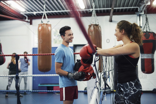 Female boxer leaning on boxing ring ropes talking to male boxer