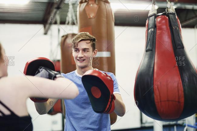 Female boxer training, punching teammate's punch mitt