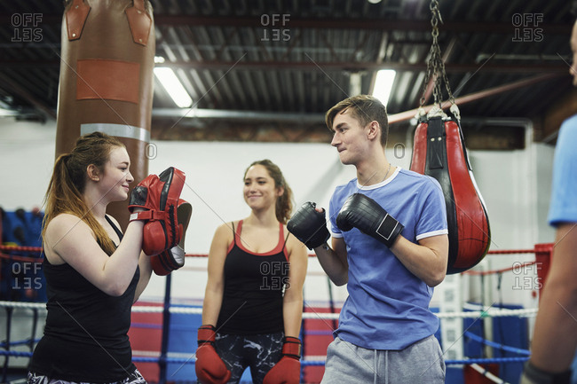Male boxer training, poised to punch teammates punch mitt