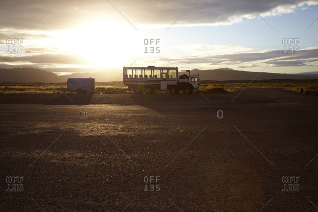 Tourist truck parked in landscape with distant mountains at sunrise, Iceland