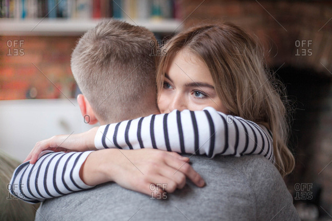 Young couple hugging, indoors, close-up
