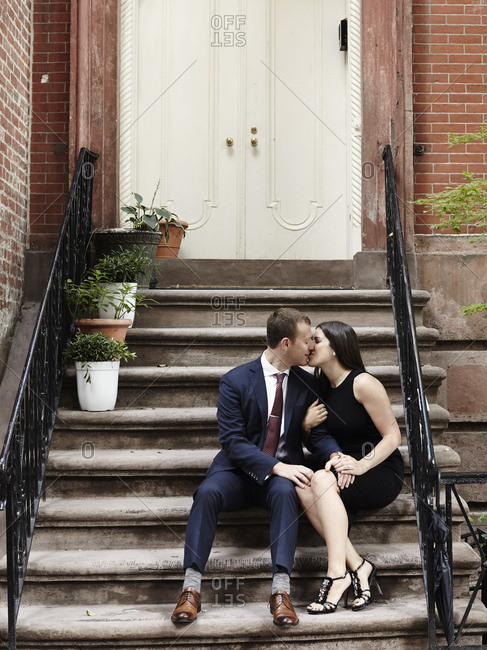 Young couple sitting on steps, kissing