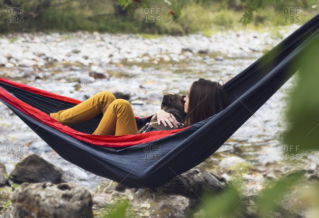 Young woman relaxing in hammock with dog, outdoors