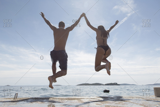 Young couple jumping into sea, rear view, Orebic, Croatia