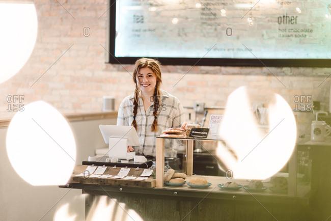 Cashier behind cash register in cafe