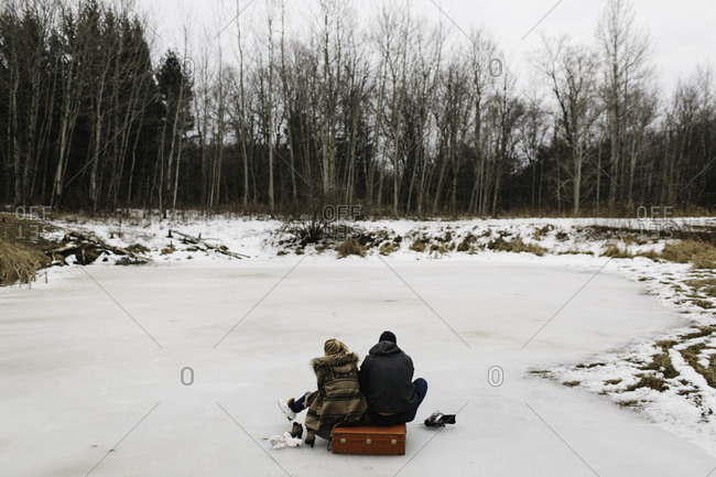 Couple sitting on red suitcase in middle of frozen lake, Whitby, Ontario, Canada